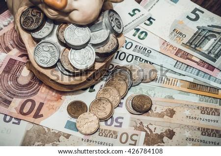 Piggybank, coins and euro bills. toned image - stock photo
