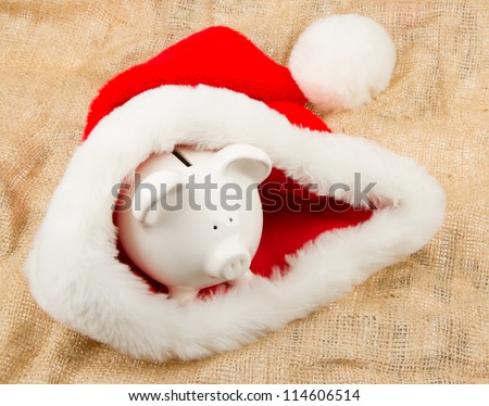Piggybank guarding Santa's crisis budget, one dollar in his hat - stock photo