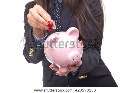 Piggybank money concept. Savings and financial concept closeup, cropped picture of business woman, hand putting money in piggy bank savings, isolated on a white background.