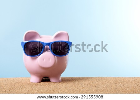 Piggybank on beach with blue sunglasses.  Travel money or retirement saving concept.  Copy space.