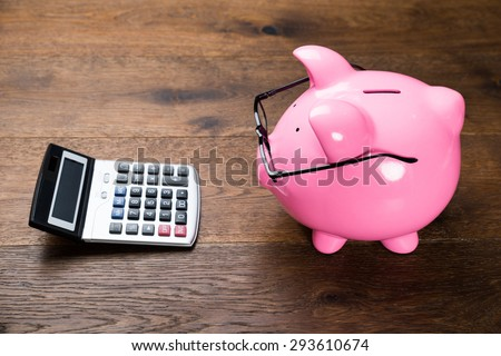 Piggybank With Eyeglasses And Calculator On Wooden Table - stock photo