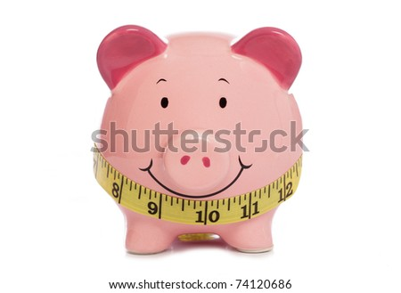 Piggybank with tape measure studio cutout - stock photo