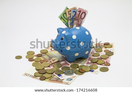 Piggybank with various banknotes and coins - stock photo