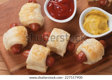 Pigs in blanket, sausage rolls with ketchup and mustard - stock photo