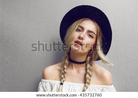 Pigtails. Close up of beautiful young blonde woman with black hat. Her hair is tied in two big ponytails. Around neck she has black choker. Professional make-up, hair style and styling.
