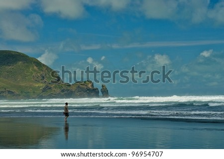 Piha beach looking south and surfing waves - stock photo
