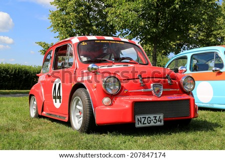 PIIKKIO, FINLAND - JULY 19, 2014: Red Fiat Abarth racing car parked on grass. Abarth began his well-known association with Fiat in 1952. - stock photo