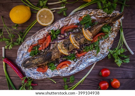 Pike baked with vegetables on the table. Wooden rustic background. Top view