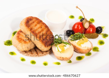 Pike cutlets with garnish on white plate