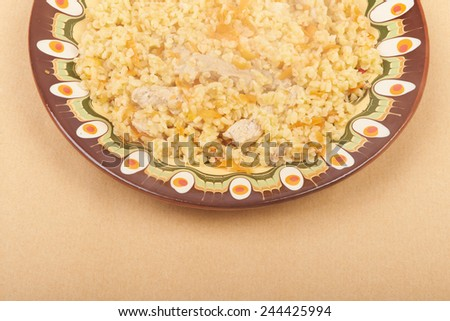 Pilaf dish, bulgur wheat with meat on ceramic plate, background - stock photo