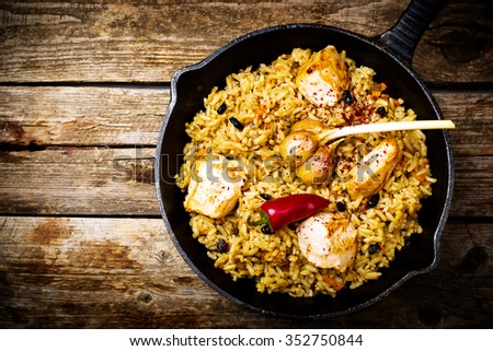 pilaf in a pig-iron frying pan. top view. style rustic. selective focus - stock photo