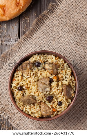 Pilaf is spicy indian food cooked with lot of rice, fried meat, carrot, onion and garlic. Served in clay bowl with raisins, fresh backed bread and vegetables - stock photo