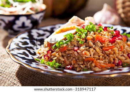 Pilaf - Rice with Chicken, Vegetables and Pomegranate. Garnished with Onions and Tomatoes Salad