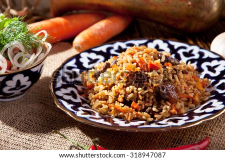 Pilaf - Rice with Meat and Vegetables. Garnished with Onions and Tomatoes Salad