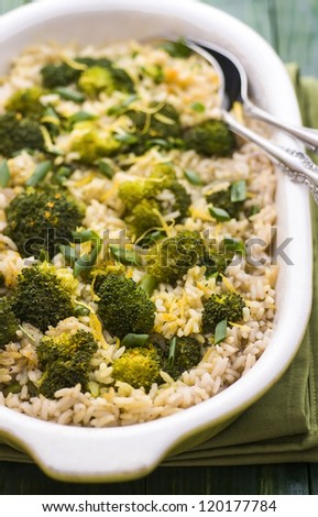 Pilaf with broccoli and lemon peel on green table - stock photo