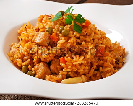 Pilaf with chicken, carrot and green peas on white plate - stock photo