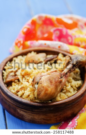 pilaf with dates, figs and chicken on a blue background. tinting. selective focus