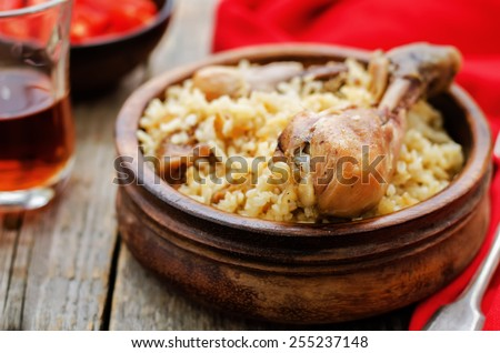 pilaf with dates, figs and chicken on a dark wood background. tinting. selective focus - stock photo
