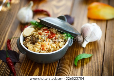 pilaf with rice and meat in a bowl on a wooden table - stock photo