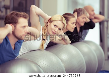 Pilates class at a gym with diverse people in a receding row exercising with their gym balls, young and elderly, men and women, with focus to an attractive blond woman