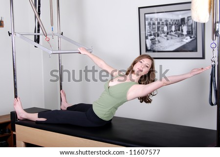 Pilates Instructor Working on Trapeze Table/Cadillac - stock photo