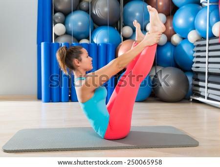Pilates Open Leg Rocker exercise on mat woman with balls background gym - stock photo