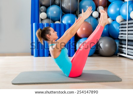 Pilates Teaser exercise woman on mat gym indoor and swiss balls background - stock photo