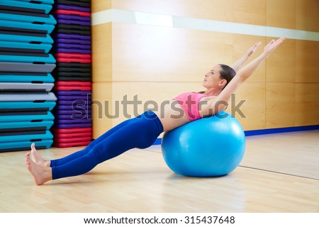 Pilates woman abdo fitball exercise workout at gym indoor swiss ball