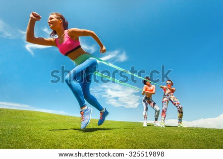 Pilates woman exercising resistance rubber band fitness workout with women coaches - stock photo