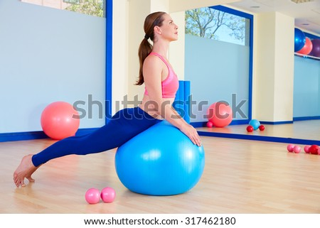 Pilates woman fitball swan exercise workout at gym indoor - stock photo
