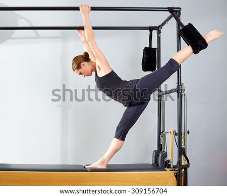 Pilates woman in cadillac split legs stretch exercise at gym - stock photo