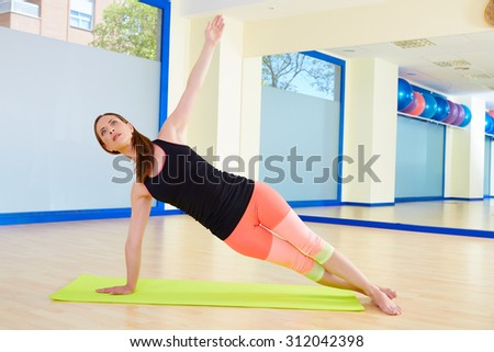 Pilates woman side bend exercise workout at gym indoor