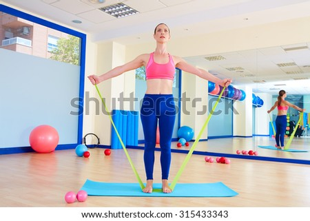 Pilates woman standing rubber band exercise workout at gym indoor