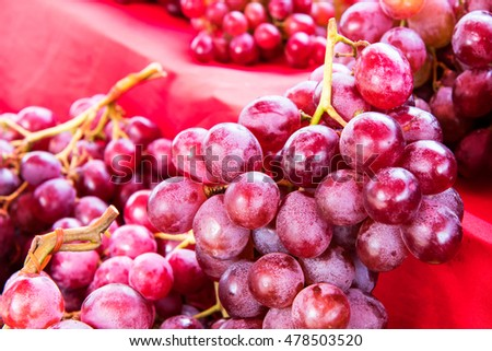 Pile a bunch of purple grapes, fruit on the table, which has many beautiful red cloth coverings are to be sold.