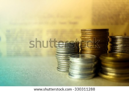 pile coins on blur newspaper background