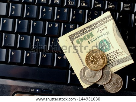 pile coins on keyboard - stock photo