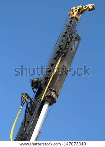 Pile-driver in action against the blue sky. - stock photo