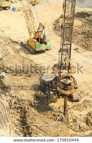 Pile driver working to set precast concrete piles at construction site - stock photo