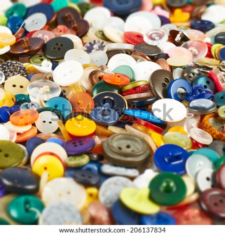 Pile of a multiple all kinds and shapes colorful buttons as a background composition with a shallow depth of field - stock photo