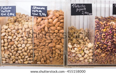 pile of almonds and pistachios in plastic containers selling in food shop - stock photo