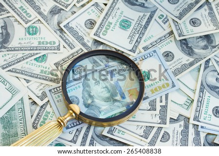 pile of american 100 dollars bills money  under manifying glass - stock photo