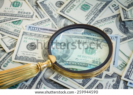 pile of american dollars money under manifying glass - stock photo