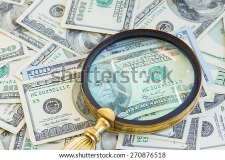 pile of american dollars money under manifying glass close up - stock photo