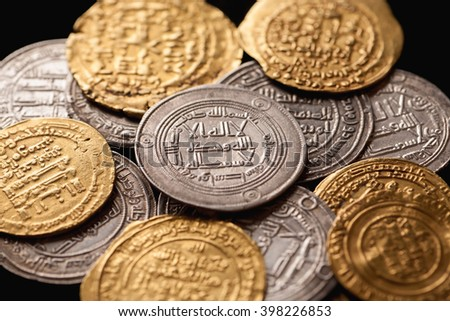 Pile of ancient golden and silver islamic coins closeup, selective focus