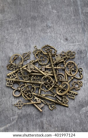 pile of antique golden keys on grunge wooden background - stock photo