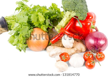 Pile of assorted farm fresh vegetables, spices and herbs with onions, broccoli, tomatoes, bell pepper, mushrooms, chilli pepper, ginger and flat leaf parsley on a white background with copyspace