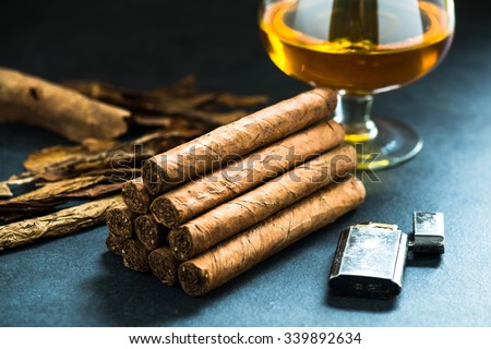 pile of authentic cuban cigars, tobacco leafs in background - stock photo