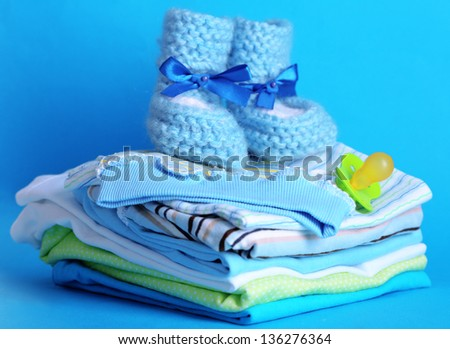 Pile of baby clothes on blue background - stock photo