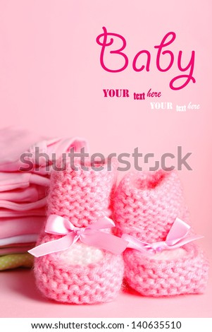 Pile of baby clothes on pink background - stock photo