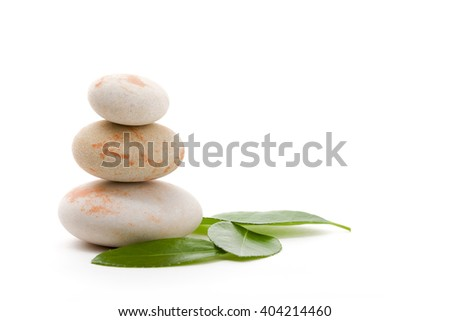 Pile of balancing pebble stones and green leaf, like ZEN stone, isolated on white background, spa tranquil scene concept with reflection - stock photo